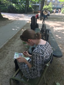 young woman sitting on bench painting in Jardin de Luxembourg