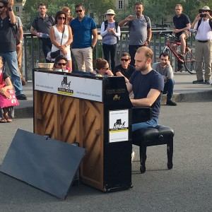 Man playing piano on bridge over the Seine