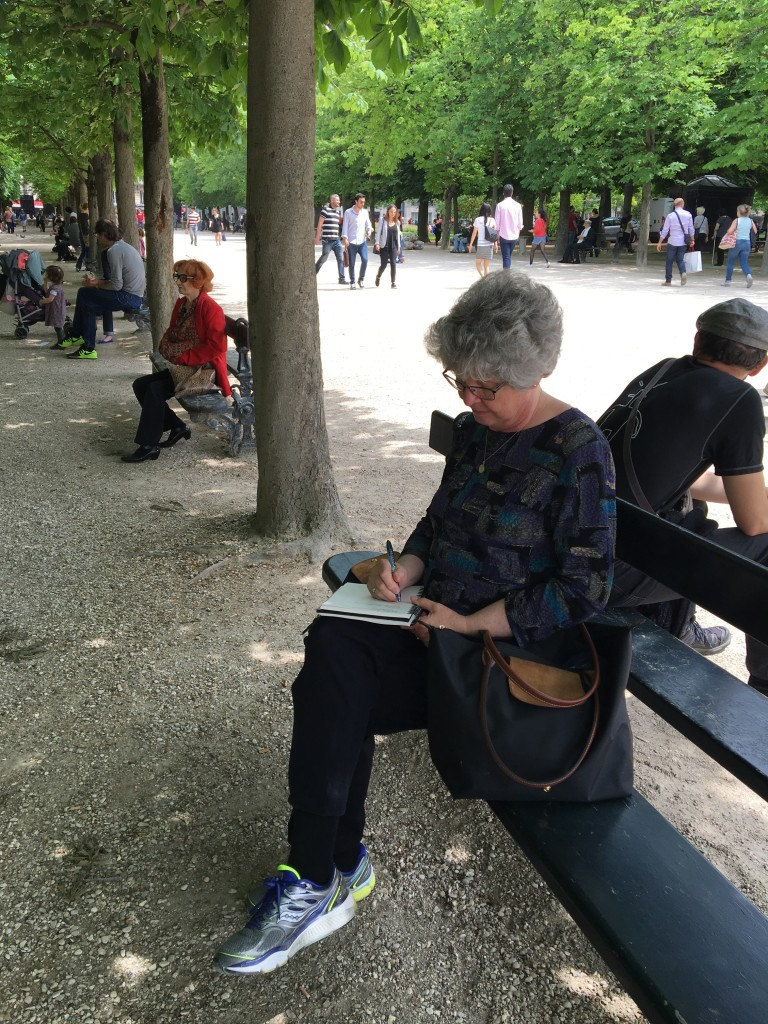 Woman on a bench in a park writing in her journal