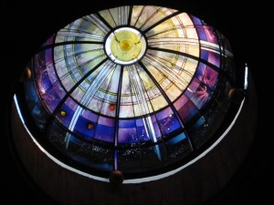 Photo of a domed stained glass window In Church in Rome, Italy, depicting the universe.