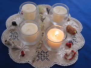 four vigil candles arranged on linen surrounded by tiny read leather pouches, feeather, shell, and other items for Advent wreathit