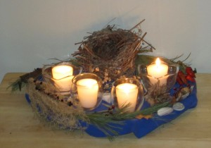Four beeswax vigil candles in glass holders, surrounded by birds nest and other natural objects used as an Advent wreath