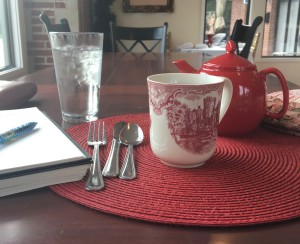 Red teapot, tea cozy, teacup, and journal and pen sitting on a wooden table.