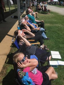 Row of people sitting in chairs holding their eclipse glasses on and gazing at the sky